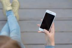 Handkvinna som använder smartphonen utanför trä Arkivbilder