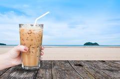 Handkvinna som rymmer det glass med is kaffet på tabellen trä med bakgrund för natur för strandlandskapsikt royaltyfri fotografi