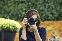 Handkvinna som rymmer kameran som tar bildbakgrund av träd och blommor royaltyfri bild