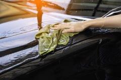 Handkvinnor rymmer vatten över bilen för tvätt med microfiber c Arkivbilder