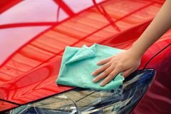Handkvinnor rymmer vatten över den röda bilen för tvätt med microfib Fotografering för Bildbyråer