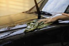 Handkvinnor rymmer vatten över den svarta bilen för tvätt med microf Royaltyfria Bilder