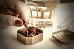 Handkvinnor tar kapslar som är röda och som är svarta i en pillerask Arkivfoton