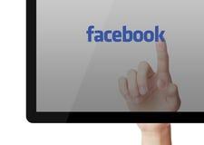 Handlag Facebook på skärmen av bärbara datorn Arkivfoton
