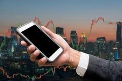Handlarskiego biznesmena chwyta mądrze telefon i rynku walutowego handlu linia Grap Obraz Stock