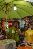 Handlarz Chodzi Ulicznego rynku Chiang Mai na telefonie przy Niedziela fotografia royalty free