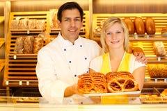 Handlarz i piekarz w piekarni teraźniejszości preclach fotografia stock