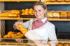 Handlarz przy piekarni kładzenia bochenkiem chleb w papierową torbę zdjęcie royalty free