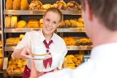 Handlarz wręcza out filiżankę herbata lub kawa w piekarni zdjęcia stock