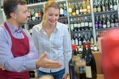 Handlarza proponowania butelek wino klient Zdjęcie Stock