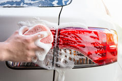 Handle car wash - male hand washing car headlight. Handle car wash - close up of male hand washing car headlight Stock Images
