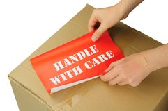 Handle with care. Hands placing handle with care label on cardboard box Stock Photography