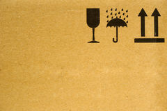 Handle with care. The symbols 'fragile', 'keep dry' and 'this way up' on the side of a cardboard box. Space for text on the cardboard royalty free stock photos