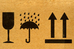 Handle with care. The symbols 'fragile', 'keep dry' and 'this way up' on cardboard Royalty Free Stock Photos