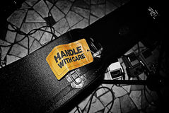 Handle with care rock style. Orange handle with care label on black guitar case Royalty Free Stock Images