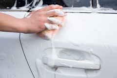 Handle carwash concept - man washing car with sponge and foam. Handle carwash concept - male hand washing car with sponge and foam Royalty Free Stock Photos