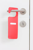 Handle of a door with a do not disturb label on it Royalty Free Stock Photo