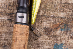 Handle of fishing rod with lure on wooden Stock Image