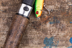 Handle of fishing rod with lure on wooden Stock Photography
