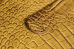 Handle of genuine leather handbag, genuine leather with embossed under the skin of reptile. Concept of shopping. Manufacturing. For background Royalty Free Stock Image