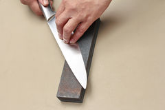 Handle the knife to make a sharp knife with a whetstone. Stock Photos