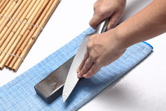 Handle the knife to make a sharp knife with a whetstone. Homemade,Maid to sharpen a knife with spray water and whetstone Stock Photos