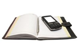 The handle and mobile phone lying on notebook Royalty Free Stock Photography