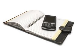 The handle and mobile phone lying on notebook Stock Photos