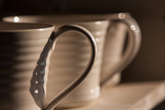 Handle of mug. Close-up photo of the handles of white mugs in half-shadow on a shelf Royalty Free Stock Photo
