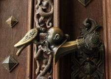 Handle. Old iron handle decorated a Turkish head with rawen pecking it´s eye (symbol from crest of Schwanzenbergs) on wooden door Stock Images