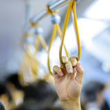 Handle on a train. People holding onto a handle on a train Royalty Free Stock Photo