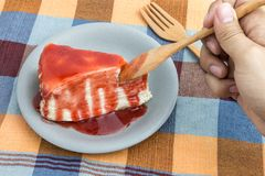Handle wooden spoon scoop strawberry jam topping on crepe cake Royalty Free Stock Images