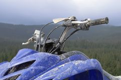 Handlebar. Dirty ATV handlebar with mountain pine forest background Royalty Free Stock Photos