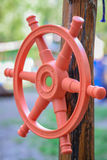 Handlebar of the ship in wooden girder. Red plastic children's handlebar of the ship a wooden girder on the playground Stock Images