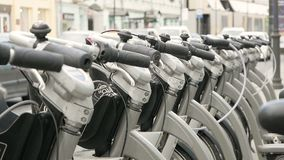Parked bikes for rent. Handlebars of parked rental bicycles in city. Convenient public transport for people in big cities who prefer healthy lifestyle. Close up stock video footage