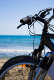 Handlebars of two bikes on the shore. Detail of the handlebars of two bikes with the sa in background Stock Photography