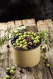 Arbequina olives from Spain. A handled enamelware pot full of arbequina olives from Catalonia, Spain, on a wooden rustic table, against a dark background with a Royalty Free Stock Photography
