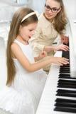 Handleda undervisar den lilla musikern att spela pianot Royaltyfria Bilder