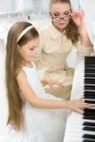 Handleda undervisar lilla flickan att spela pianot Royaltyfri Fotografi