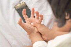 Handleden smärtar och sammandragningen av musklerna Bruk av telefonen royaltyfria bilder