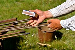 Handles of branding irons heating up. Hands holding a match box reach out to move iron handles heating up for a roundup and branding session royalty free stock image