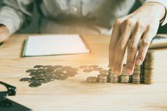 Businessman Handles coins placed on a pile of money on the table royalty free stock photo
