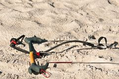 Extreme sport, kiteboard hand bars and cables in sand. Handles and safety cables for kiteboarding in sand of a tropical beach on a stormy, windy, autumn day and Royalty Free Stock Photos