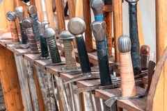 Handles swords of ancient ages in a row.  royalty free stock photos