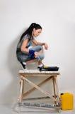 Handliche junge Frau, die ihr hoause malt Stockbild