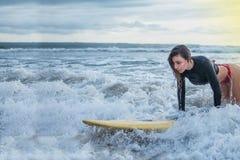 Handling av den unga kvinnan försöker att kliva att stå på surfingbrädan i meden av havet som rider på utbildningen för vågattemp royaltyfri fotografi