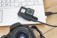 Handling-kamera förbindelse till en bärbar dator, på bakgrunden av en trätabell med en yrkesmässig kamera arkivfoto