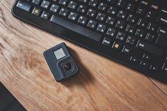Handling-kamera på bakgrunden av ett svart tangentbord på en trätabell arkivfoton