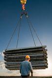 Handling load lifting operations. Laborer and pallets in steel rope at handling load lifting operations Royalty Free Stock Photography