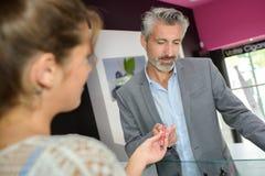 Handling over an e-cigarette. Woman stock photos